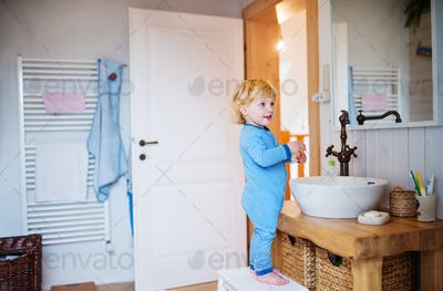 Cute toddler boy standing on a stool in the bathroom.