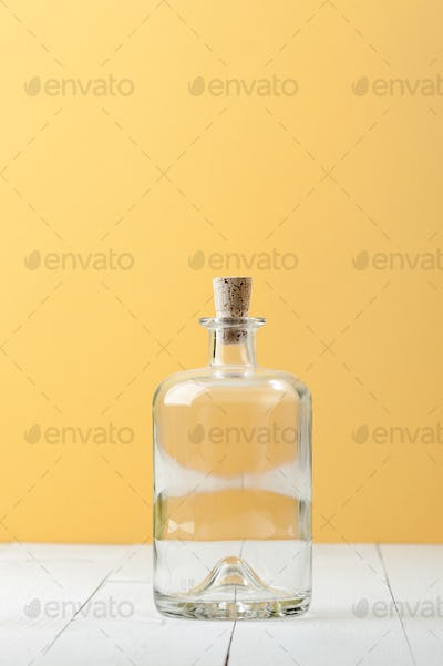 Empty glass bottle for rum on a light white-yellow background.