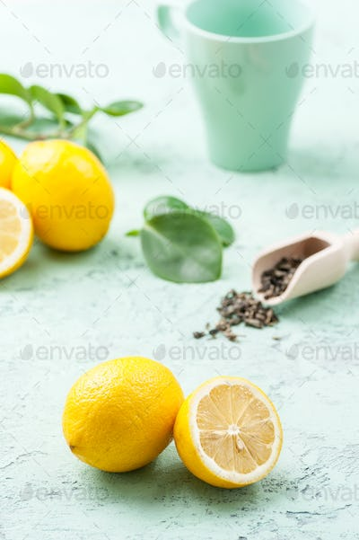 Ripe lemons, tea leaves and a cup on a mint-blue background.
