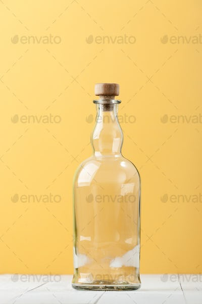 An empty relief glass bottle on a light white-yellow background.