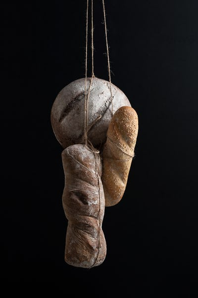 Three kinds of bread hang on a scaffolding on a black background