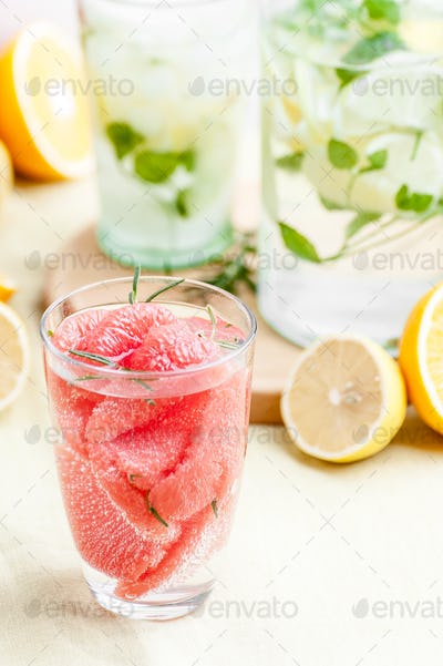 A glass of lemonade with grape seed slices, soda water and lemon