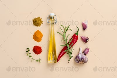 Olive oil, herbs and spices on a light beige background.