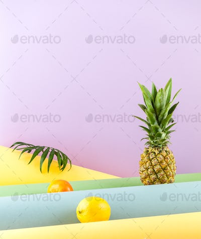 Pineapple, lemon and mandarin on a combined colored background.