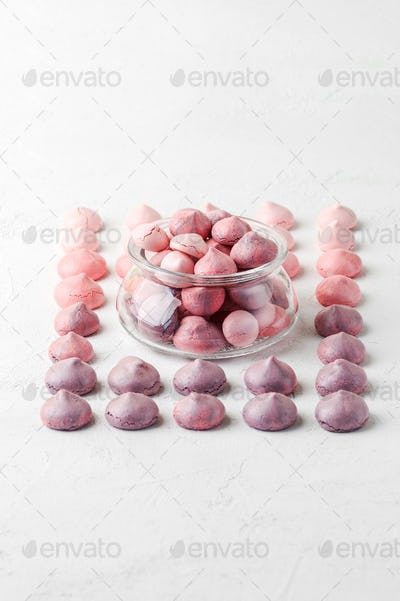 Multicolored meringues in violet-pink colors in a glass jar and