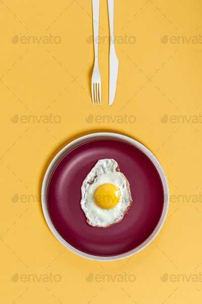 Fried egg on a burgundy plate on a yellow background. Breakfast