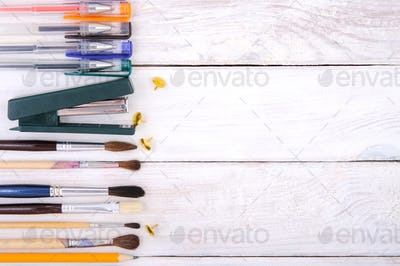 Stationery on a white wooden plank table.