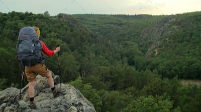 caucasian hiker standing on a rocky peak