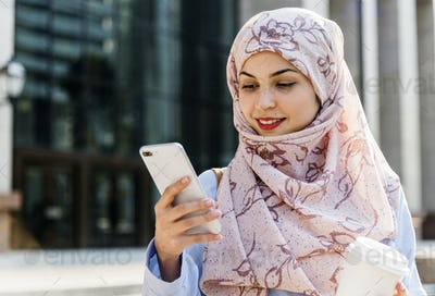 Islamic woman using mobile phone and holding coffee cup