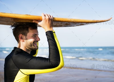 A man carrying a surfboard