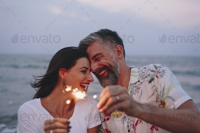 Couple celebrating with sparklers at the beach