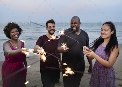 Friends celebrating with sparklers at the beach