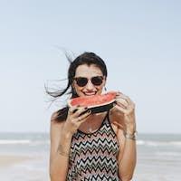 Woman eating watermelon at the beach