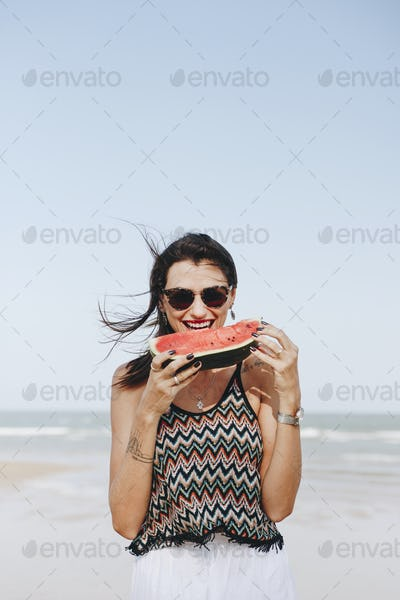 Woman eating watermelon at the beach