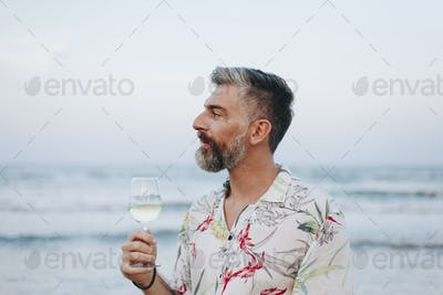 Man drinking a glass of wine by the beach
