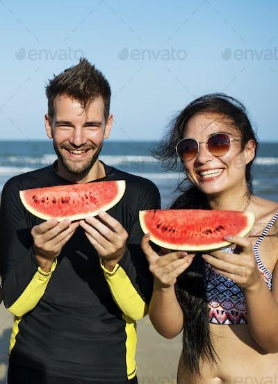 Couple eating watermelon on summer beach