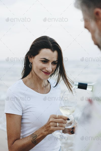 Couple enjoying a glass of wine by the beach