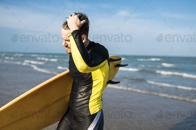 A man carrying a surfboard