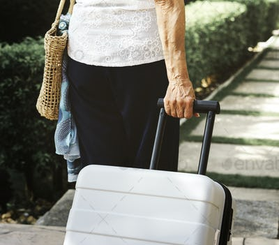 Senior woman pulling a suitcase