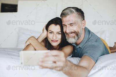 Honeymooners taking a selfie in bed
