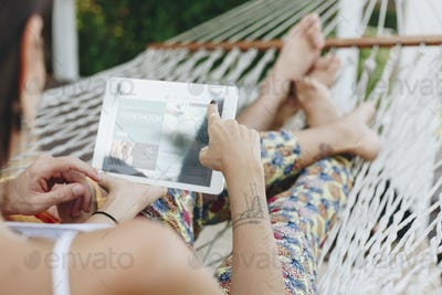 Couple using a tablet in a hammock