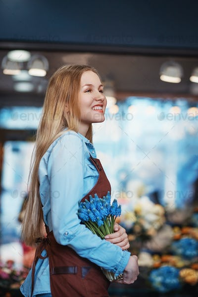 Smiling woman with muscari indoors