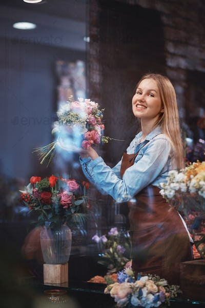 Smiling young florist in uniform