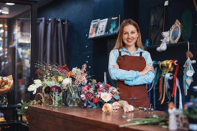 Smiling florist with flowers at the counter