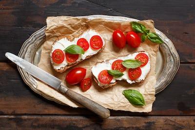Bruschetta with cream cheese, cherry tomatoes and basil