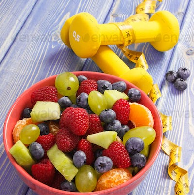 Fruit salad and centimeter with dumbbells, healthy lifestyle and nutrition concept
