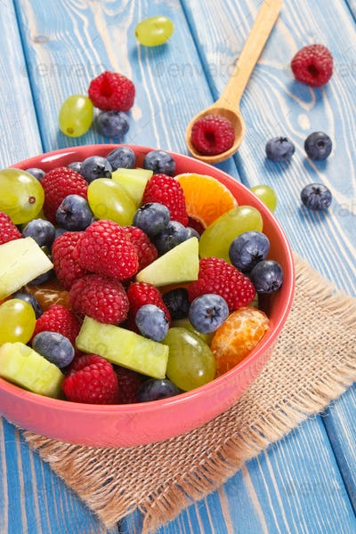 Fresh prepared fruit salad in glass bowl, healthy nutrition concept