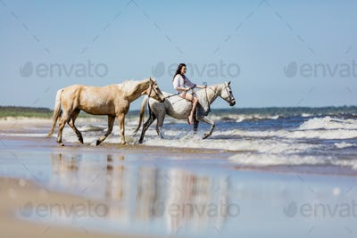 Young girl with two horses riding into the sea.