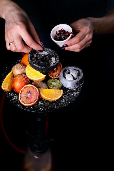 Women's hands put fruit tobacco in a hookah on a black background