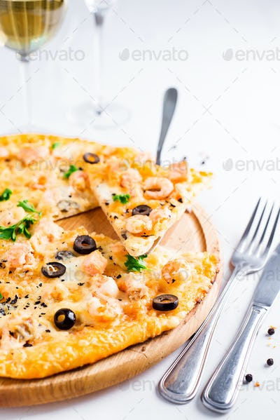 Fresh baked pizza hawaii with with pineapple, salmon and shrimp on wooden plate
