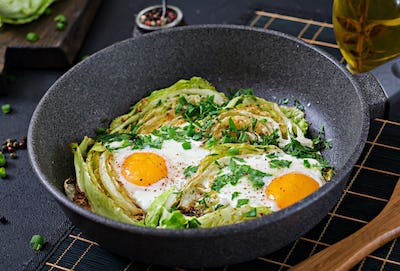 Fried eggs with slices of young cabbage and greens. Nutritious breakfast.