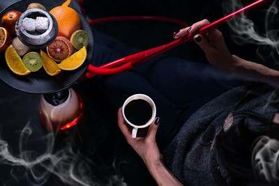 A girl with a cup of coffee in her hands smokes a hookah