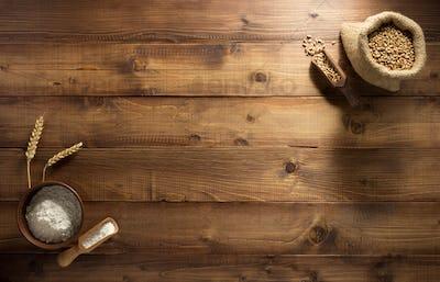 ears and wheat flour on wood