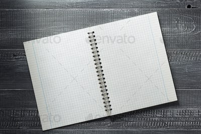 checked notebook at wooden  background