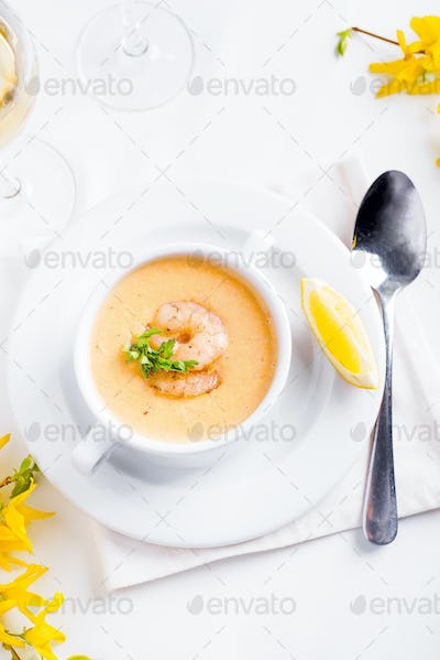 Creamy pumpkin soup with seafood and lemon on a white background.