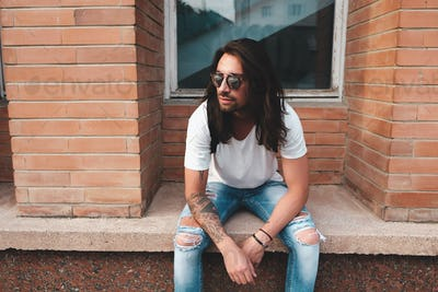 Portrait attractive man near window on urban background