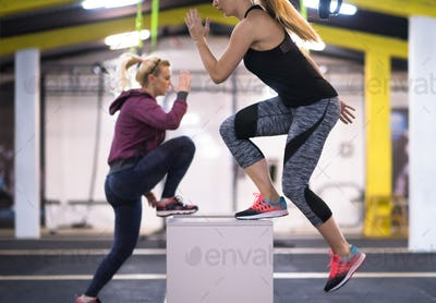 athletes working out  jumping on fit box