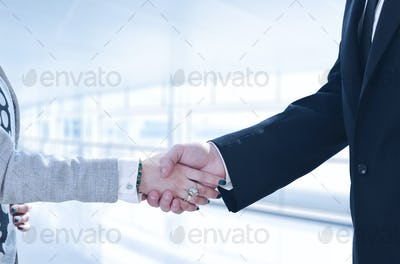Businessman and businesswoman shaking hands after meetup