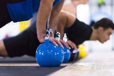 young athletes doing pushups with kettlebells