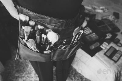 Professional makeup artist with a belt bag with makeup brushes.
