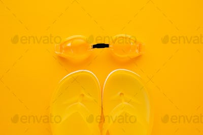 Swimming goggles and flip flops on yellow background
