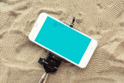 Smartphone on selfie stick in beach sand