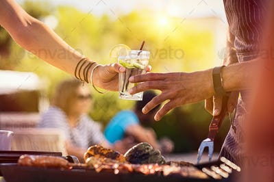Woman sharing drink at bbq