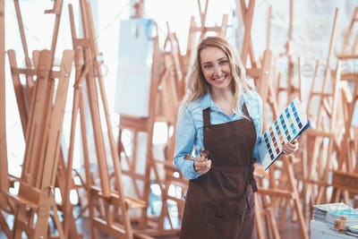 Happy young woman with easels