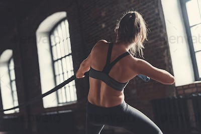 Sporty girl pulling a rope