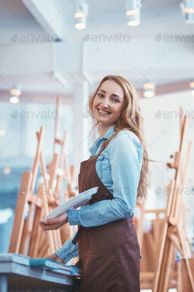 Happy young artist with easels